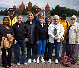 Photo of 10 people standing together to have their picture taken. In the background is a body of water, and on the other side of the water is a castle.