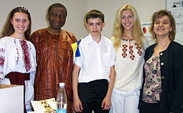 Photo of three students and two adults standing together in a room to have their picture taken.