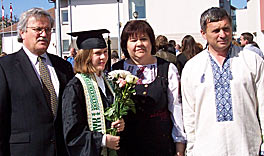 Photo of Eric Hinderliter with a young woman wearing cap and gown and two older people. Though they are posing for a picture together, all their eyes are looking at something to the right of the camera.
