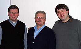 Photo of Eric Hinderliter and two young men. One man wears a clerical collar. All three men are wearing dark sweaters and smiling for the camera.