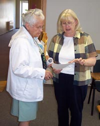 Photo of two women standing together reading from a piece of paper.