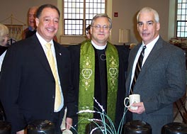 Photo of three men standing in a church. The one in the middle wears a clerical robe and green stole.