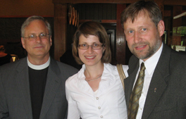 A woman stands between two men. The man on the left is wearing a clerical collar.