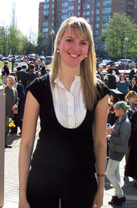 A young woman, standing among a crowd of graduates and attendees of a graduation ceremony.