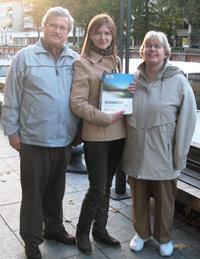 A young woman holding a book, standing between a man and a woman, outside.