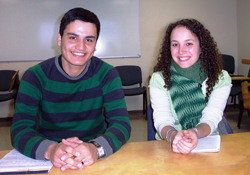 A young man and young woman, both wearing green-colored clothing, sitting at a table.