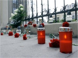 Photo of lighted candles and flowers along a fence.