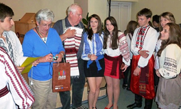 A man and a woman present gifts to a group of young people in traditional dress.