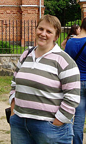 Photo of a woman standing in front of a church and smiling for the camera. She seems relaxed and has her hands in the pockets of her jeans.