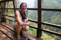Photo of Tracey kneeling on a brigde with the valley in the background.