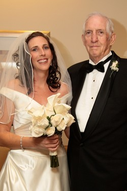 Photo of Tracey in a wedding dress standing next to a man in a tuxedo and black bow tie.