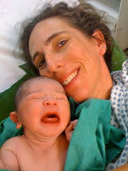 Photo of Tracey in a bed holding a newborn baby that appears to be crying.