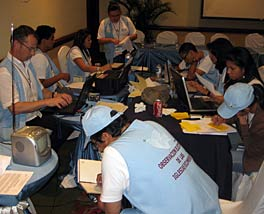Photo of eight people working around a large table inside a room. All are wearing matching light-blue bests. A radio can be seen prominently on the table.