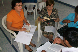 A small group of women, sitting in a circle, holding Bibles.