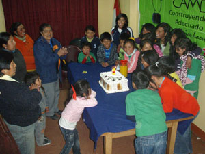A group of people around a table with a cake, celebrating.
