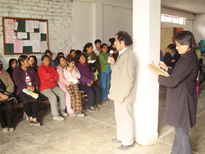 A man speaks to a group of women, as a woman behind him holds an open Bible.