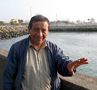 Photo of a man standing beside a waist-high wall beside a body of water. He wears a jacket and an open-collar shirt and is making a gesture with his left hand.