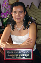 "Photo of a young woman sitting at a desk. In front of her is a standing plaque on the desk that says ""Dyna Maira Escobar Alcaldesa Municipal El Palmar."""