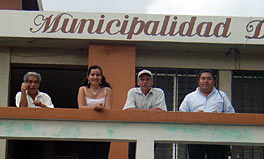 Photo of Dyna Maira Escobar standing at the railing of a balcony with three men.
