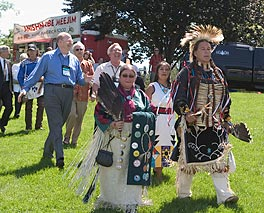 Photo of several people on a lawn; some are wearing Native American dress