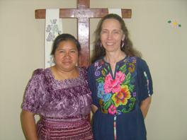Juana Herlinda Yac Salanic and Karla Ann Koll standing together in front of a wodden cross draped with white decorated cloths.