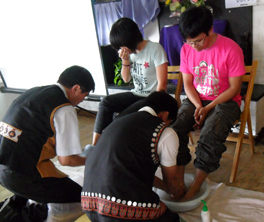 Choon Lim and another man washing the feet of two young people