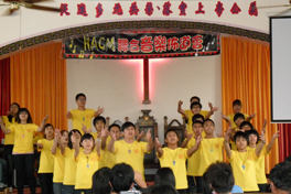 A group of young people wearing yellow T-shirts holding their outstreched arms toward an audience.