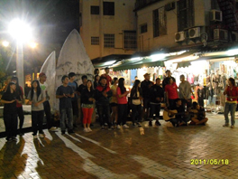 A group of young people, standing on a street in worship.