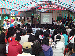Photo of a small sanctuary, perhaps in a tent, full of people. Along the side some people can be seen wearing colorful clothes.
