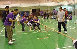 Photo of a group of students pulling on a thick rope. Presumably, another group of students outside of the picture frame is pulling in the opposite direction. Two men stand next the rope where a red ribbon is tied and appear to be watching the ribbon intently.