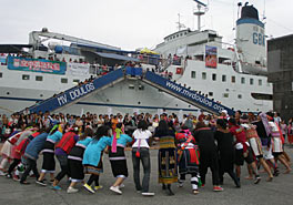 A circle of people are dancing in an open space on the pier in front of a large white ship.