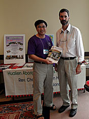 Photo of Choon standing with a man. The two are posing in front of a table about the Hualien Aboriginal Christian Ministry.