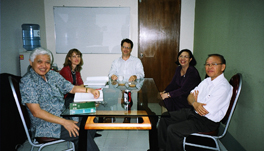 A group of people at a table in a classroom.