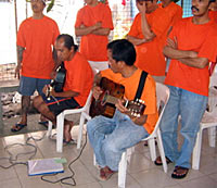 Photo of seven men wearing orange tee shirts and blue jeans. Two of them sit and hold guitars. The others stand behind them, their arms folded over their chests.