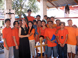 Photo of 18 people standing in a courtyard in front of a cross. There are two children among them. Except for the children and Mary Nebelsick, all the people are wearing bright orange tee shirts.