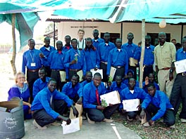 Photo of a group of people, most of whom are wearing blue shirts and holding papers