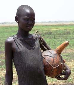 Photo of a young girl standing in a field with a gourd held from her shoulder by netting.