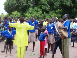 Photo a group of people wearing blue shirts; one persoh carries a drum. A woman dressed in yellow faces them, apparently directing a song.
