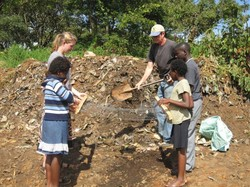 Photo of Jim holding a shovel and the kids holding a screen, apparently to use as a seive for screening compost.