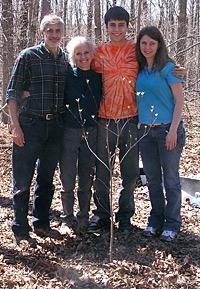 Photo of the Morgan family standing in a wooded glen with their arms around each other, smiling. The sun is bright. In the foreground is a dogwood tree about four-feet high just beginning to leaf.