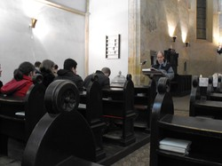Photo of the inside of a church; a person is reading at a lectern to people sitting in the pews.