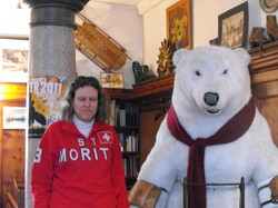 Photo of Karen Moritz standing next to a statue of a white bear with a scarf around its neck.