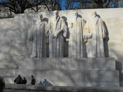 Photo of wall with statues of four men in front of it.