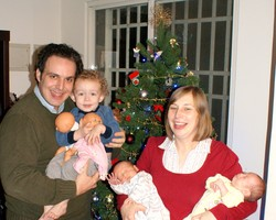 Photo of Jonathan holding Sam and Emily holding the twins; behind them is a decorated Christmas tree.