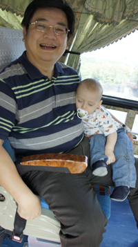 A baby sitting and sleeping on the lap of a man.
