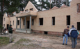 Photo of a one-story building made of yellowish bricks. Four men are standing in front of it. The building is unfinished: no windows, no roof.