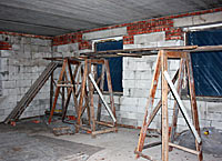 Photo of the corner of a room. Scaffolding stands before two windows, which have been covered in black plastic.