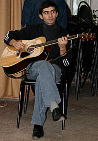 Photo of a young man sitting on a chair holding a guitar. His right leg is crossed over his left leg and his eyes are looking off camera to his left.