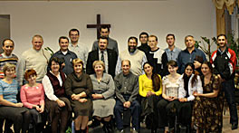 Photo of 22 people standing in two rows to have their picture taken. They are inside, perhaps in a chapel or church. There is an (empty) wooden cross on the wall behind them.