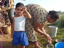 Photo of a young boy standing in front of a woman who is bending over to wash her hands in bucket.
